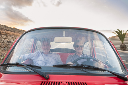 nice adult couple drive and love inside a red old vintage car parked on the road. smiles and have fun traveling together. happiness and lifestyle for nice people. summer time and vacation journey