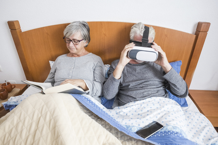 nice beautiful couple caucasian matures man and woman at home in the bedroom stay on the bed during a morning. she read a paper book and he play and use goggles headset trying new technology experience