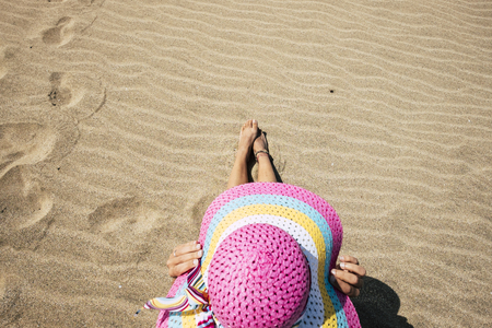 aerial point of view from above with nice beautiful caucasian lady protect his body from the sun with a pink big hat. sitting on the beach and making a sunbath. holiday and travel destination concept