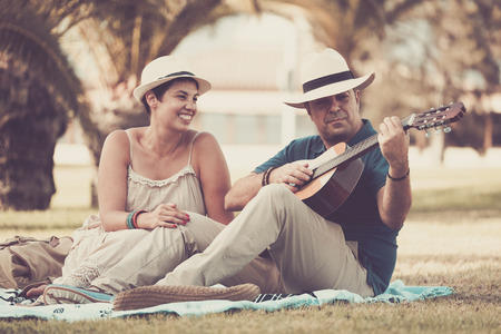 happy middle age caucasian couple man woman enjoying the outdoor leisure activity staying together and playing an acoustic guitar. music and enjoyment concept for beautiful people sitted on the grass 写真素材