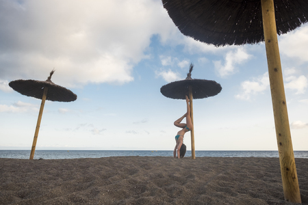 beautiful young female in reverse yoga position at the beach. sand and exercise in outdoor. sexy and thin babe with long legs in summer time doing exercise to stay health and build a perfect body