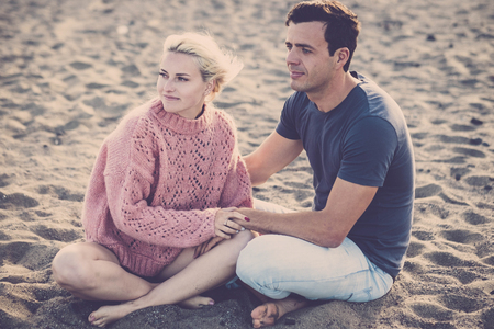 beautiful model couple caucasian young lady and man stay in love hugging and sitting on the beach. blonde and black hair in relationship outdoor leisure activity. vacation and lifestyle concept enjoying nature and travel