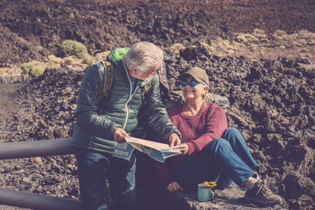 couple adult senior man and woman trekker explorer during a rest over the mountains drinking a tea or coffee and looking at the paper map to choose the nex direction of her trip. people in wanderlust enjoy life Stock fotó