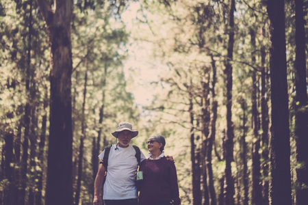 Indie couple of travelers adult senior retired couple in love forever together walking in the middle of an high trees pines forest hugged and happy for their alternative lifestyle. choosing to live free