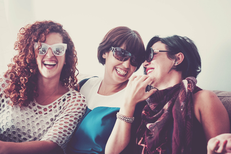 three young crazy females friends having a lot of fun at home on the sofa. all of them with sunglasses and laughi and smiles. close contact for best friendship. joy and people smiling, vintage colors 免版税图像