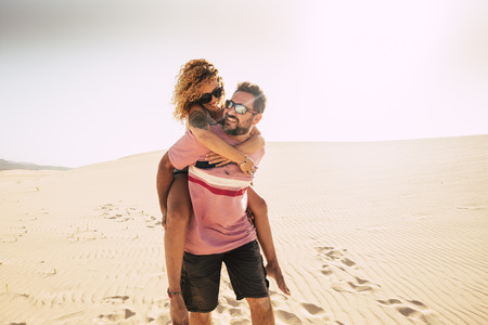 happiness concept with middle age people man carrying woman on his back walking on the soft sand of the desert dunes in totally freedom. alternative vacation and happy lifestyle