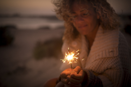 beautiful lady use and look a sparkly fire light in a summer night. beach and ocean defocused in the background. travel and vacation concept for a dreamer female middle age