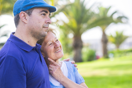 different ages couple like mother and son stay hugged together in outdoor leisure activity with love and emotions. enjoy the day in the park with green plants tropical background. bright colors Foto de archivo