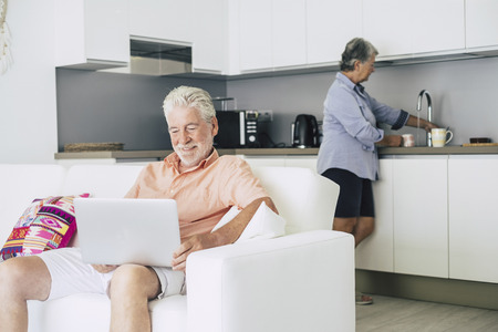caucasian people aged senior adult couple at home. man working or watching a movie on the internet laptop and woman taking a cup of tea in the kitchen. life at home for retired people