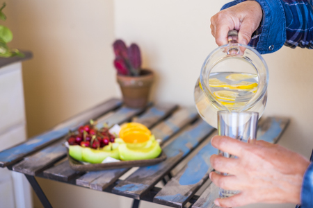closeup with woman hands put diet detox water in a glass to drin for mature people at home. Fresh fruit on a table in the background