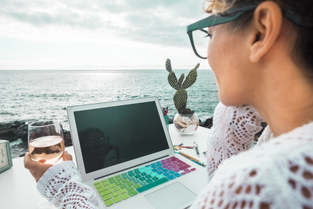 free digital nomad woman at work with a laptop sitting in front of the ocean in free outdoor space like alternative kind of closed office. Working with technology in nature place with freedom for people 版權商用圖片