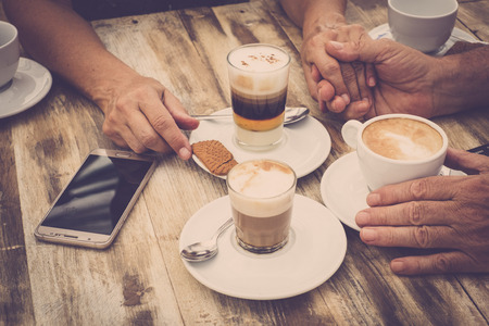 Close-up of hands with coffee cups and mobile phone in a cafe with wooden tables - food and beverage morning breakfast in shabby chic design - senior hands with love Stock Photo