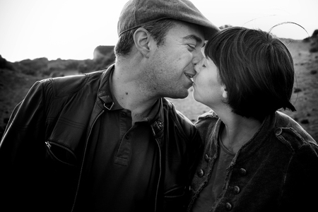 romantic kiss for etherosexual caucasian middle age couple in black and white colors - love and life together concept for people outdoor - first date or married concept - happiness kissing
