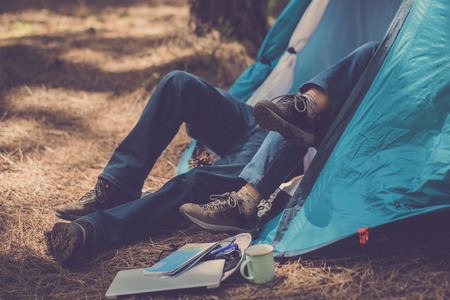 couple of hikers trekker enjoy the tent inside with love and partnership together. laptop and map outside ready to start and enjoy the exploration and the vacation. outdoor activity lifestyle enjoying life