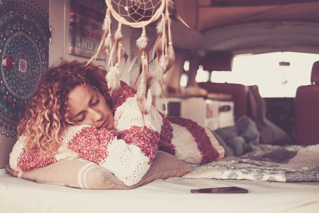 woman with curly hair and warm sweater sleeping and dreaming on home van, lulled by the sea breeze. Concept of independence, relaxation, travel, leisure time - dreamcatcher and vintage filter Stockfoto