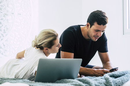 Young millennial modern couple at home in the bedroom morning time use technology devices like phone and laptop to check social media on internet - freelance everywhere work for alternative worker