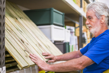 Caucasian man choose articles in hardware store - wood floor like pallets to build furnitures or ground at home - business concept for retired people like to do activities