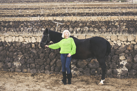Blonde attractive european caucasian young middle age woman pose standing up with a beautiful black dark horse. Country wall background and fashio style pict concept