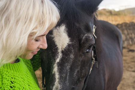Face to face blonde attractive pretty model and beautiful amazing power black horse stay together in friendship and love. Animal therapy and alternative couple lifestyle Foto de archivo
