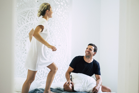 nice cute young couple in hotel room playing and having fun together on the bed - white minimal home and beautiful people laugh and smile in the morning with love and relationship concept Stock Photo