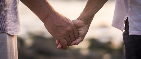 valentine's day love over time concept with hands of man and woman mature old people aged taking together each other with defocused background - romance and romantic picture for retired life 版權商用圖片