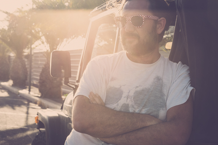 Man middle age with sunglasses standing near off road car parked in tropical street with sun in backlight - sunset atmosphere for nice caucasian people - travel concept