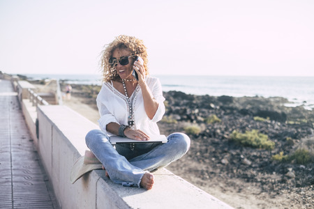 Cheerful beautiful middle age caucasian woman with curly hair smile and speak on the mobile phone sit down near the ocean in technology outdoor activity. yoga crossed legs and laptop for modern people at work