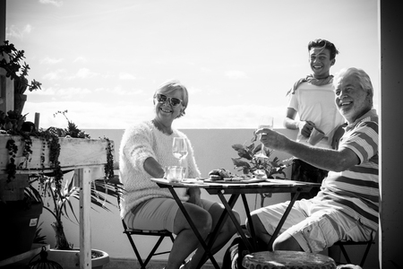 elderly mature adults and a young boy stay on the terrace having fun together. summer vacation time concept with people enjoy the place