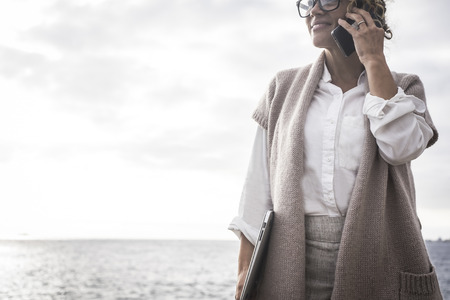 Caucasian middle age lady manager business woman work outdoor with ocean in background like free freelance with perfect lifestyle digitla nomad concept speak at the phone using internet connection worldwide everywhere