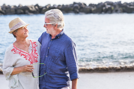 aged caucasian couple beautiful man and woman white hair and hat walk together at the beach enjoying the new retired adult life third age with freedom from work and offices