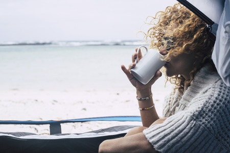Beautiful middle age woman sit down inside a tent in free beach camping outdoor feeling the nature while drink a tea or coffee from a white cup - wind in her hair and freedom concept for alternative lifestyle