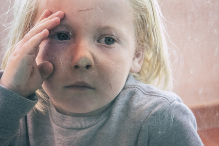 little children blonde hair with cut on his front looking inside through the glass of a door. curiosity and protect concept for innocent young boy. blue eyes and blonde hair caucasian child