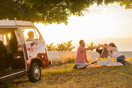 Family and friends all together in picnic leisure activity on a meadow with a red old vintage van parked and son children inside loooking them clinking with some beers during a coloured golden sunset