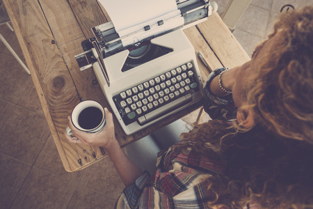 Above view of curly woman thinking and taking coffee with old typewriter on the table ready to write a book or a message in past way - alternative artistic work for independent modern strong lady - hipster wanderlust conceptual image Stock fotó