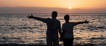 Valentine's day concept with couple in silhouette enjoying red coloured beautiful sunset together opening arms and having joy with nature outdoor leisure activity - tourists in front of the ocean in the evening