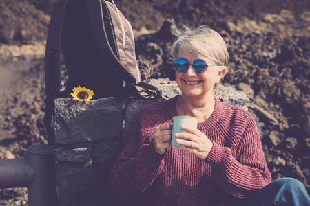 Cheerful happy caucasian aged mature woman enjoy a hot beverage like tea or coffee resting after a trekking day of outdoor leisure activity at the mountain - alternative vacation lifestyle
