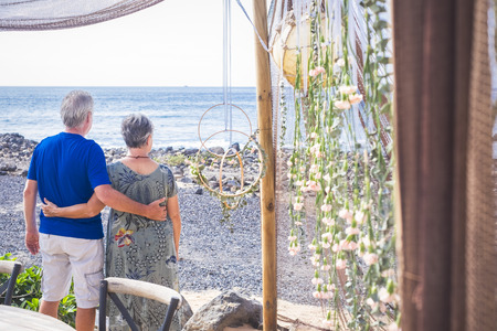 Retired couple in relationship looking at the sea during summer spring vacation together - happy leisure outdoor activity for married aged people with ocean in background - tourists concept at the beach