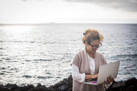 Modern woman manager work with internet and laptop everywhere without needed an usual office - alternative digital nomad lifestyle with internet and a laptop - working with ocean in background for success business concept