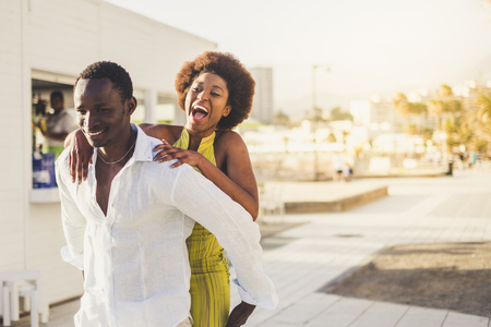 Happy cheerful attractive black skin african couple enjoy the outdoor leisure activity in the city. The man carry the laughing girl on his back. Beautiful millennial people love and play together