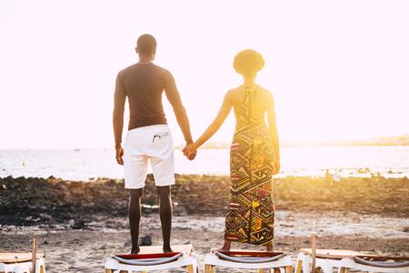 Romantisches schwarzes Paar verliebte afrikanische Leute, die den Sonnenuntergang betrachten, während sie im Sommerurlaub oder im Meer-Lifestyle auf Sonnenperlen am Strand aufstehen. Menschen in romantischer Freizeitbeschäftigung Standard-Bild