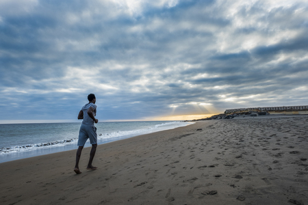 young black race african man run over the beach in fitness activity outdoor near the ocean and nature and sunset around him. healthy lifestyle for happy people enjoying the world and the life