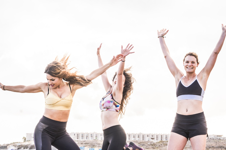 Three caucasian girls doing exercise and fitness on the beach Stock Photo