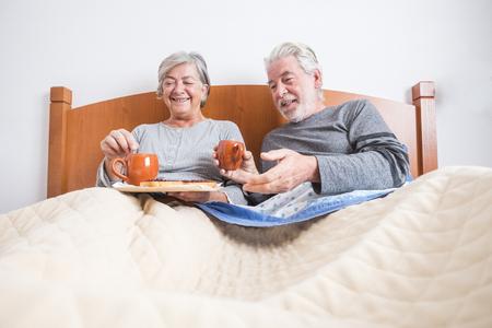 Pareja de adultos mayores en casa desayunando juntos en la cama por la mañana - actividad interior para personas casadas - vista al suelo y hombre y mujer divirtiéndose en el dormitorio