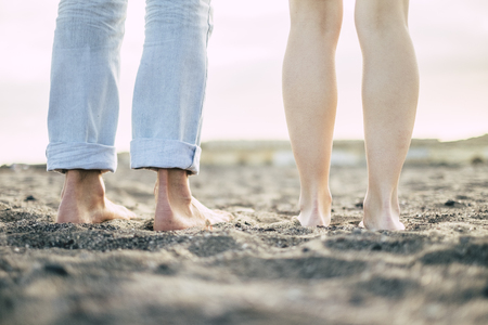 ground and rear view of feet from man and woman couple in friendship or relationship - naked nude young bodies enjoying the sand at the beach - naturism concept for alternative vacation Banque d'images - 116705526