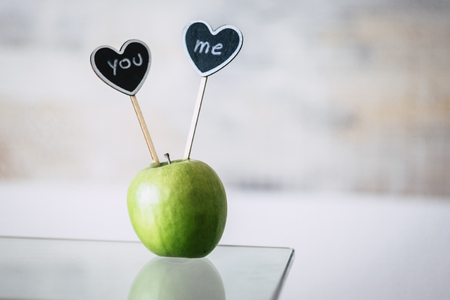 Love concept with green apple on the table and two black hearts with you and me writtin on it - valentine's day perfect image Imagens