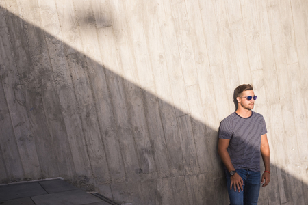 attractive young man standing  near some urban staris and looking at the sun. shadow and light composition for attractive people concept in the city