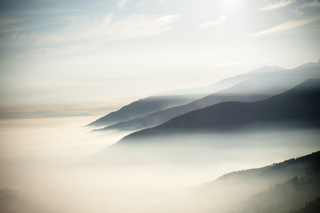 early morning at the top of the mountains looking an amazing scenery panorama with clouds like fog that hidden the valley
