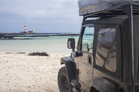 big off road vehicle from black high strong car explore the beach and look at the lighthouse in background. alternative way of travel and lifestyle for traveler in wanderlust Stock fotó