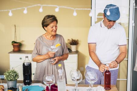 Madre e figlio che preparano la cena per gli amici a casa aprendo una bottiglia di vino rosso - felici di incontrare persone -