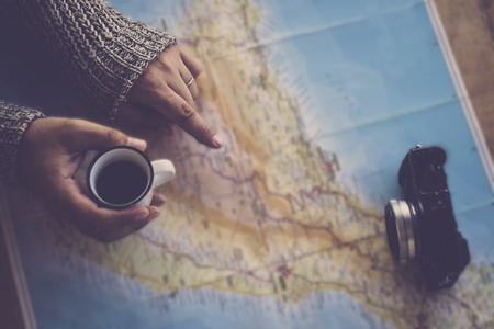 Dark tones travel wanderlust image concept with top view of woman hands looking and pointing on the next trip paper map - coffee and camera ready to start for the next adventure for alternative lifestyle people 写真素材